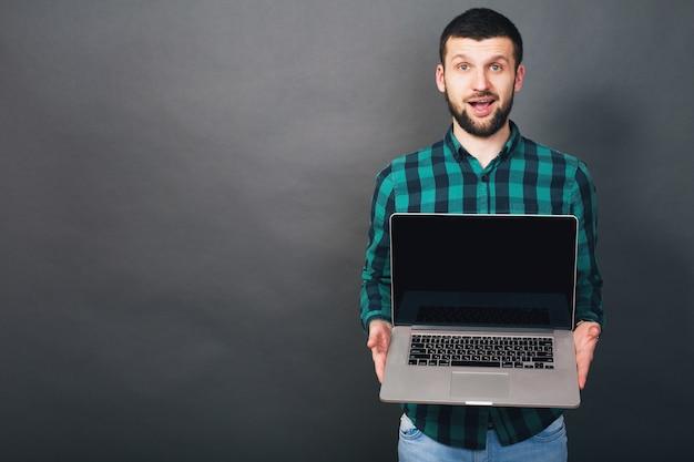 Jonge knappe hipster bebaarde man met laptop in handen, groen geruit overhemd, positieve emotie, gelukkig, glimlachen, verrassing, grijze achtergrond Gratis Foto