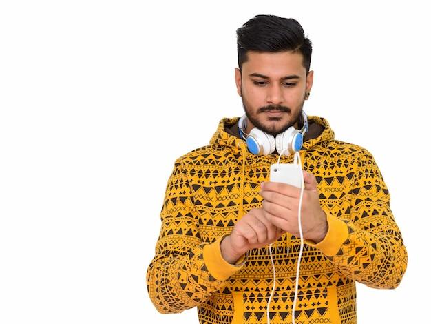 Jonge knappe indiase man met behulp van mobiele telefoon met koptelefoon Premium Foto