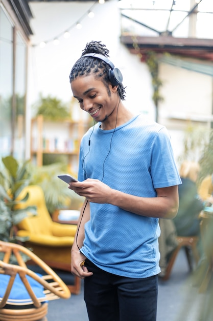 Jonge knappe jongen luisteren muziek van zijn smartphone Premium Foto