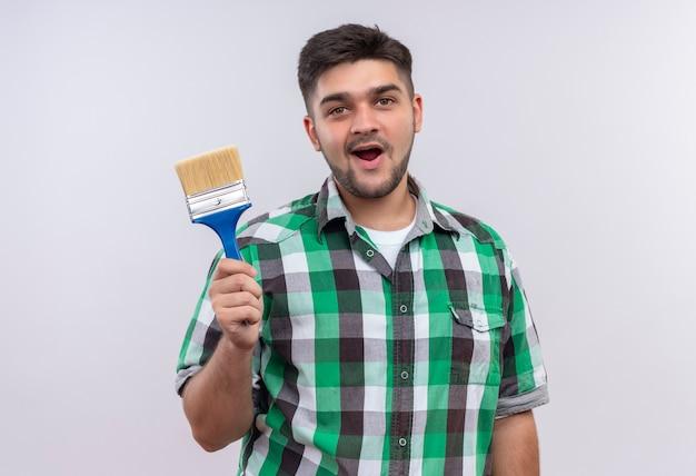 Jonge knappe kerel die de geruite verfborstel draagt die van de overhemdsholding tevreden zich over witte muur bevindt Gratis Foto