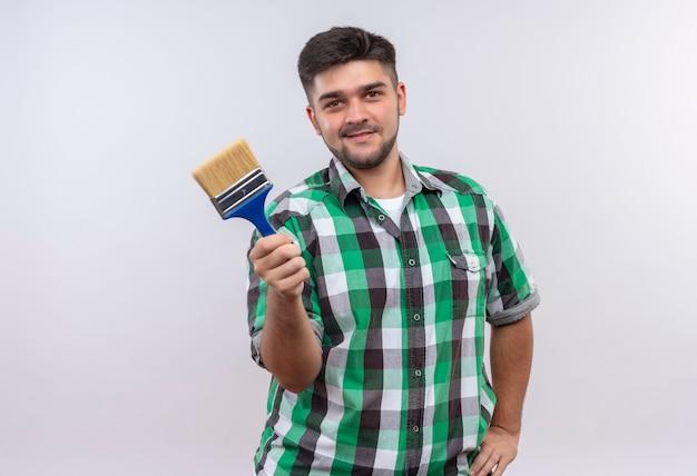 Jonge knappe kerel die geruit overhemd het glimlachen houden verfborstel die zich over witte muur bevinden Gratis Foto