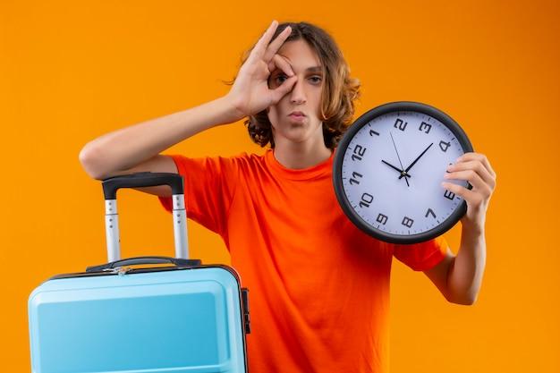 Jonge knappe kerel in oranje t-shirt met reiskoffer en klok die ok teken doet met hand die door dit bord kijkt met vertrouwen serieuze uitdrukking op gezicht dat zich over gele pagina bevindt Gratis Foto