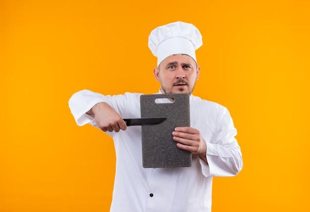 Jonge knappe kok in chef-kok uniforme bedrijf snijplank en mes geïsoleerd op oranje ruimte Gratis Foto