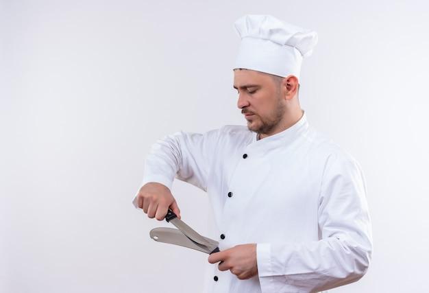 Jonge knappe kok in eenvormige chef-kok die mes en hakmes wrijft dat op witte ruimte wordt geïsoleerd Gratis Foto