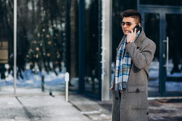 Jonge knappe man buiten het gebruik van de telefoon Gratis Foto
