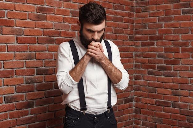 Jonge knappe man denken poseren op bakstenen muur. Gratis Foto