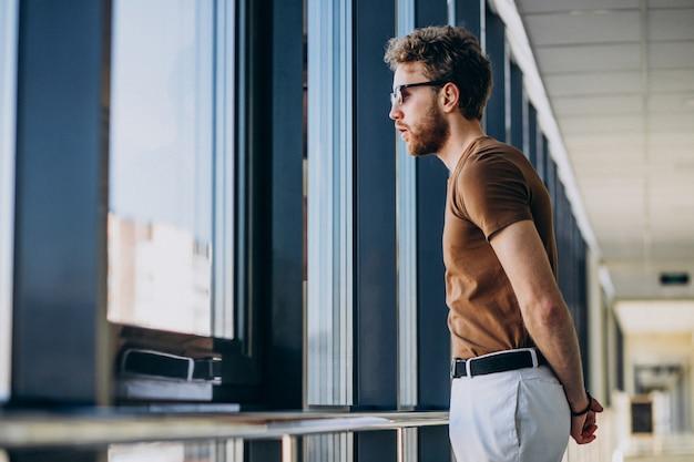 Jonge knappe man die bij het raam op de luchthaven Gratis Foto