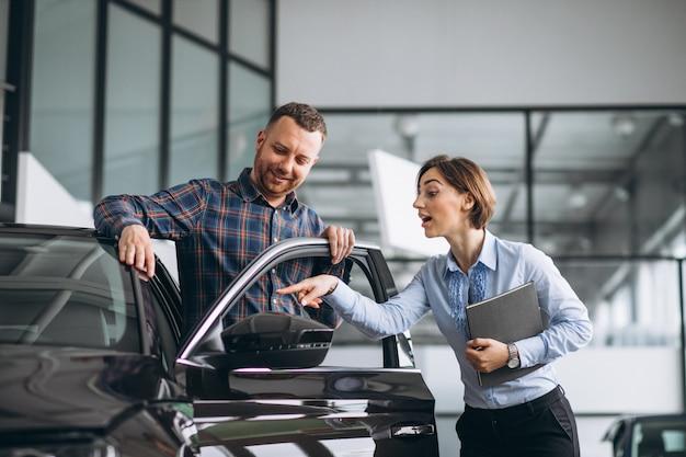 Jonge knappe man die een auto in een autotoonzaal kiest Gratis Foto
