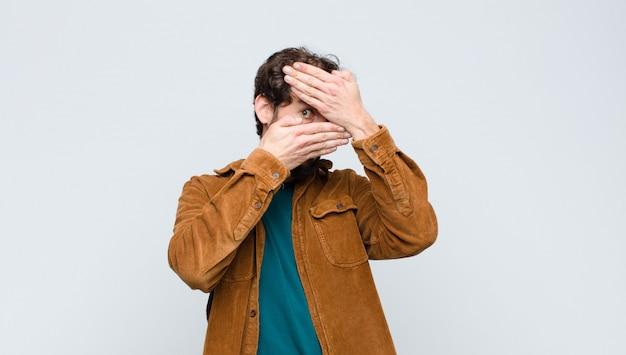 Jonge knappe man die gezicht bedekt met beide handen nee zeggen tegen de camera! afbeeldingen weigeren of foto's over de muur verbieden Premium Foto