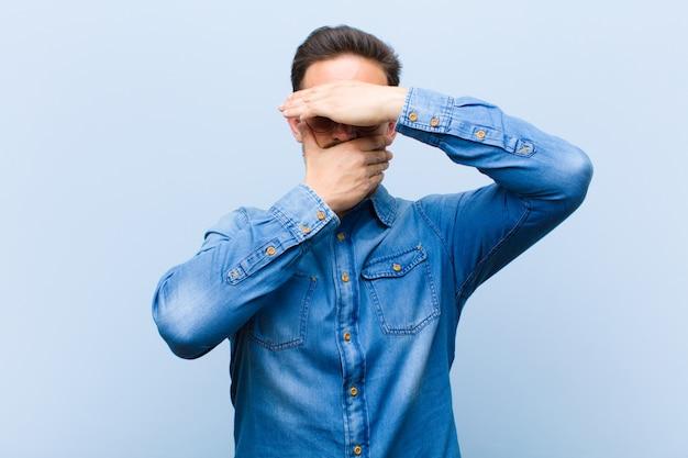 Jonge knappe man die het gezicht bedekt met beide handen en nee zegt tegen de camera! afbeeldingen weigeren of foto's verbieden Premium Foto
