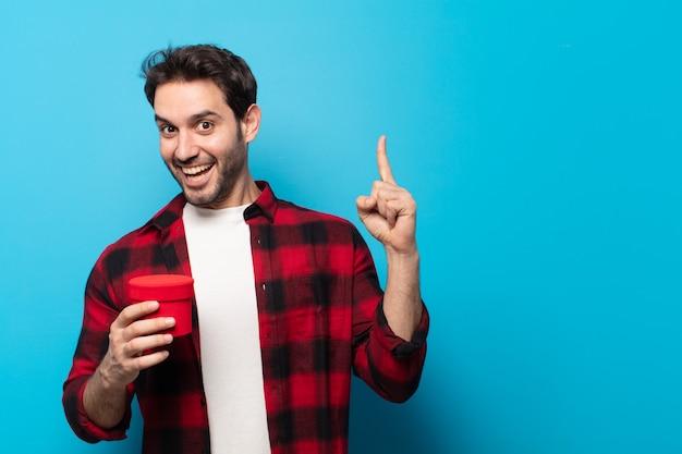 Jonge knappe man die zich als een gelukkig en opgewonden genie voelt na het realiseren van een idee, vrolijk de vinger op te steken, eureka! Premium Foto