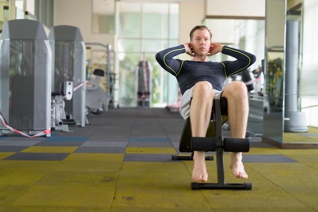Jonge knappe man doet sit-ups in de sportschool tijdens covid-19 Premium Foto