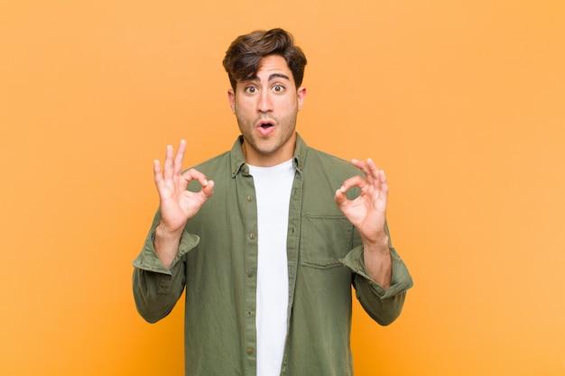 Jonge knappe man geschokt, verbaasd en verrast voelen, goedkeuring tonen goed teken maken met beide handen tegen oranje muur Premium Foto