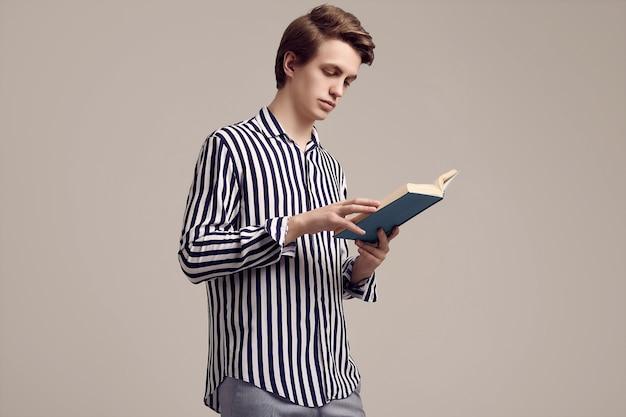 Jonge knappe man in gestreepte shirt lezen van een boek over grijs Premium Foto