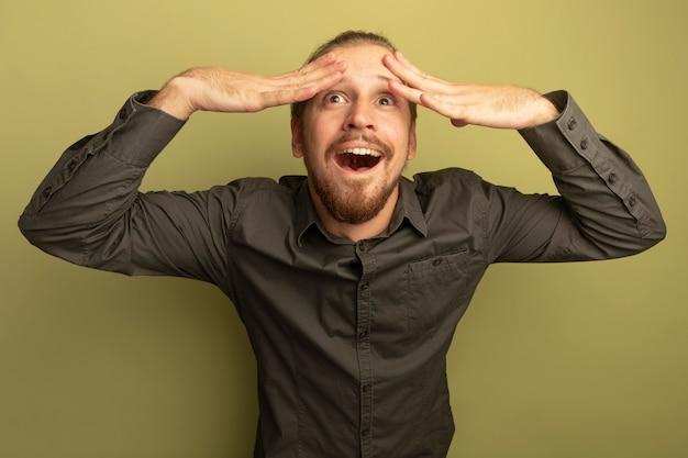 Jonge knappe man in grijs shirt blij en opgewonden met handen op zijn hoofd opzoeken Gratis Foto