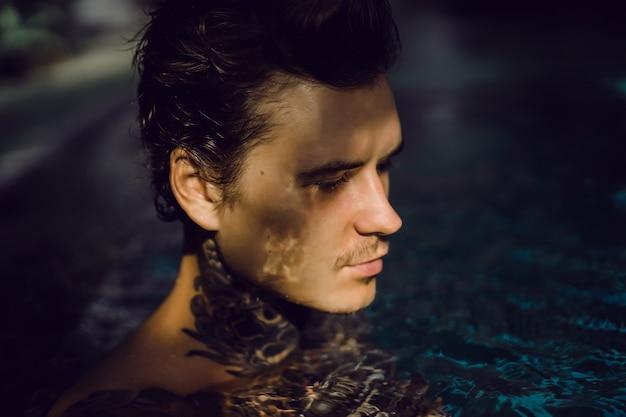 Jonge knappe man in tatoeages rusten in het buitenzwembad. Gratis Foto