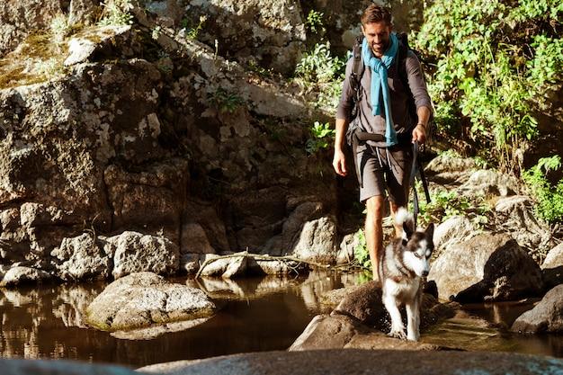 Jonge knappe man lopen met huskies hond in canyon in de buurt van water Gratis Foto