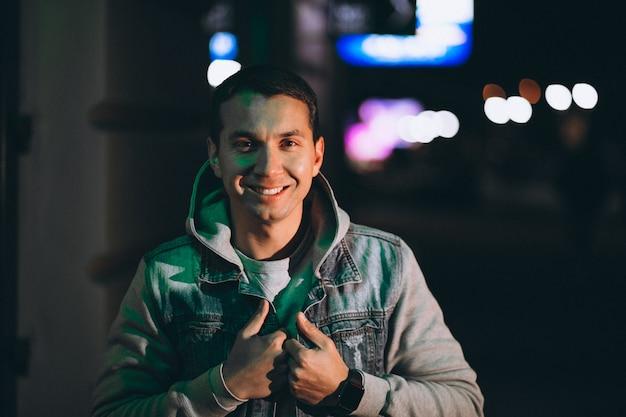 Jonge knappe man lopen 's avonds buiten de straat Gratis Foto