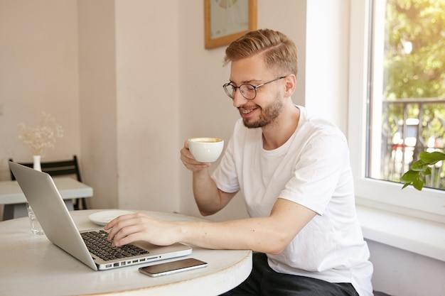 Jonge knappe man met baard zit aan tafel in café en drinkt koffie tijdens het typen van tekst op zijn laptop, glimlachend en in een goede bui Gratis Foto