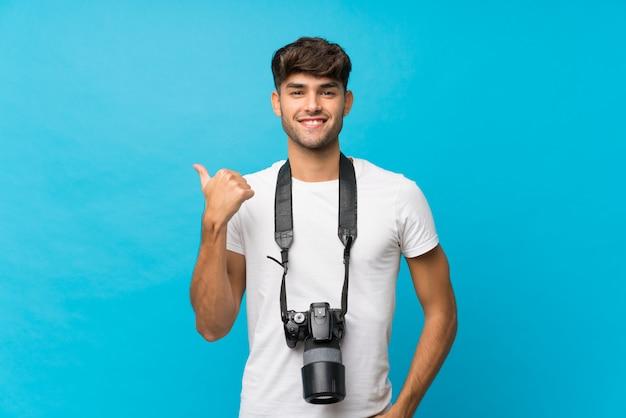 Jonge knappe man met een professionele camera en wijst naar de kant Premium Foto
