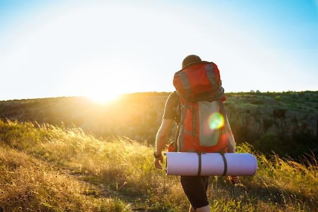 Jonge knappe man met rugzak reizen in canyon bij zonsondergang Gratis Foto
