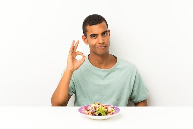 Jonge knappe man met salade in een tabel met een ok bord met vingers Premium Foto
