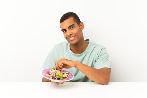 Jonge knappe man met salade in een tafel Premium Foto