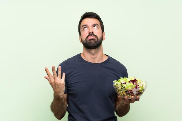 Jonge knappe man met salade over geïsoleerde groene muur gefrustreerd door een slechte situatie Premium Foto