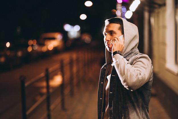 Jonge knappe man met telefoon 's nachts in de straat Gratis Foto