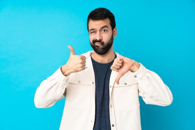 Jonge knappe man met wit corduroy jasje over geïsoleerde blauwe muur die goed-slecht teken maakt. onbeslist tussen ja of niet Premium Foto
