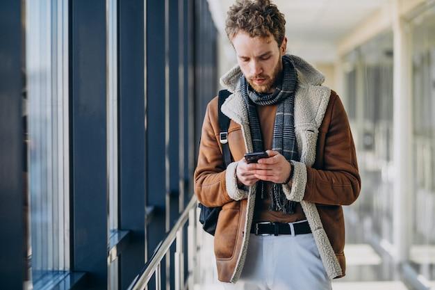 Jonge knappe man op de luchthaven praten aan de telefoon Gratis Foto