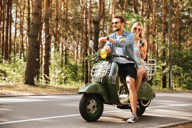 Jonge knappe man op scooter met vrouw met camera Gratis Foto