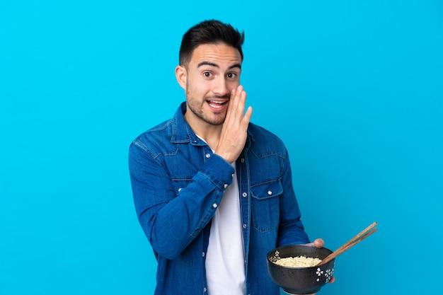 Jonge knappe man over blauw iets fluisteren Premium Foto