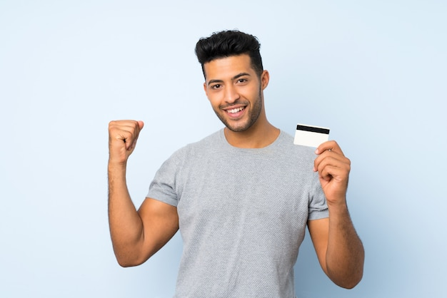 Jonge knappe man over geïsoleerde achtergrond met een creditcard Premium Foto