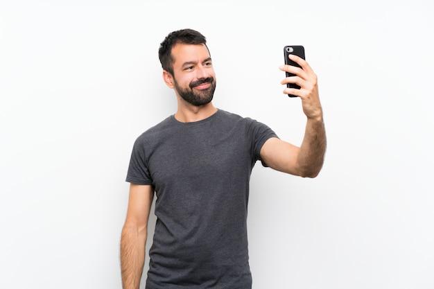 Jonge knappe man over geïsoleerde wit maken van een selfie Premium Foto