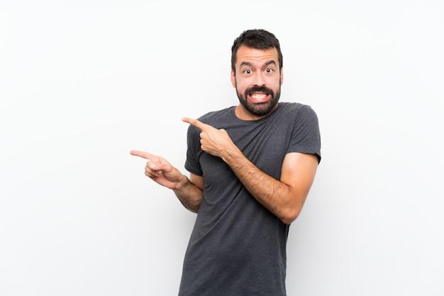 Jonge knappe man over geïsoleerde witte muur bang en wijzend naar de kant Premium Foto