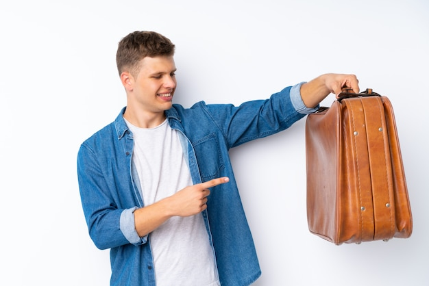 Jonge knappe man over wit met een vintage koffer Premium Foto
