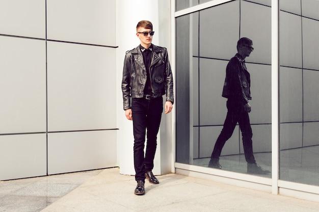 Jonge knappe man poseren in de buurt van moderne zakencentrum, stijlvolle leren puntige jas, zwarte spijkerbroek en zonnebril, brutale look. Gratis Foto