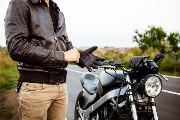 Jonge knappe man poseren in de buurt van zijn motor, het dragen van handschoenen. Gratis Foto