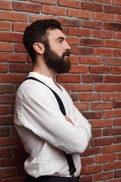 Jonge knappe man poseren met gekruiste armen op bakstenen muur. Gratis Foto