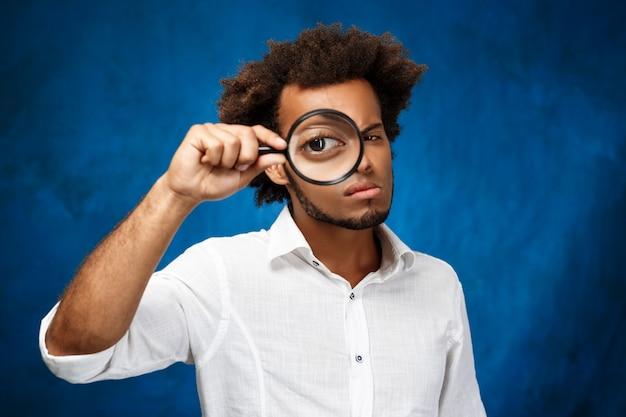 Jonge knappe man poseren met vergrootglas over blauwe oppervlak Gratis Foto