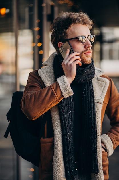 Jonge knappe man praten over telefoon door de luchthaven Gratis Foto