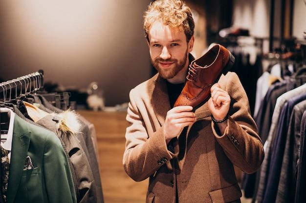 Jonge knappe man schoenen kiezen in een winkel Gratis Foto