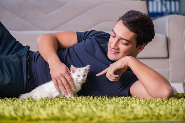 Jonge knappe man spelen met witte kitten Premium Foto