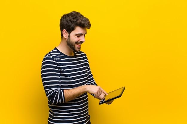 Jonge knappe man tegen oranje achtergrond Premium Foto