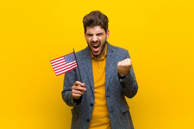 Jonge knappe man tegen oranje muur Premium Foto