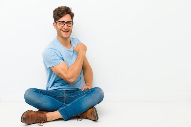 Jonge knappe man voelt zich gelukkig, tevreden en krachtig, buigt fit en gespierde biceps, ziet er sterk uit na de sportschool op de vloer zitten Premium Foto