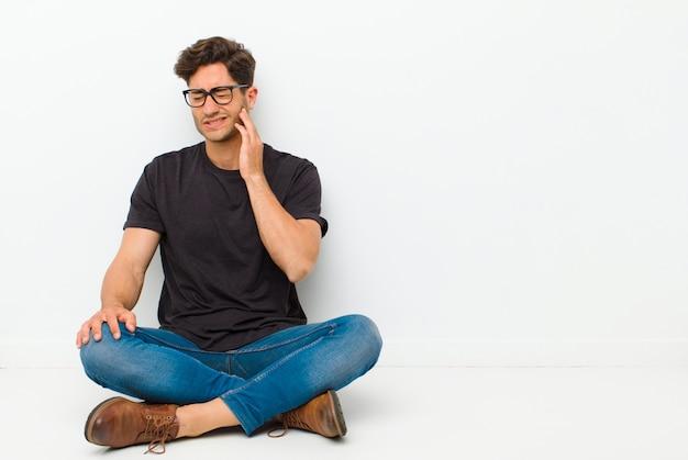 Jonge knappe man wang houden en pijnlijke kiespijn lijden Premium Foto