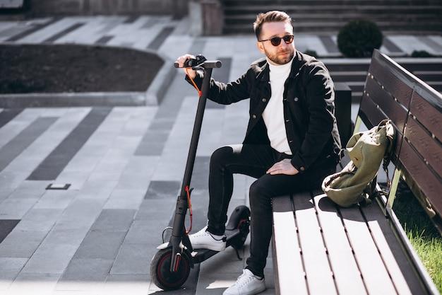 Jonge knappe man zittend op de bank in het park, rust van een scooter rijden Gratis Foto