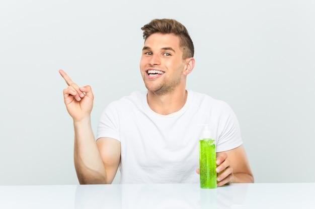 Jonge knappe mens die een fles van aloëvera houden glimlachend vrolijk richtend met weg wijsvinger. Premium Foto